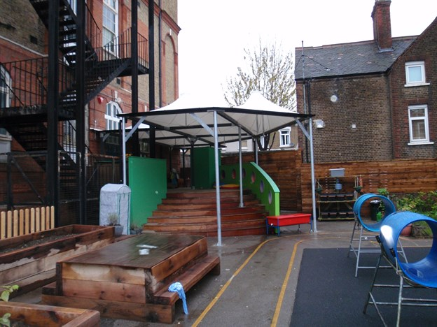 Shade canopy covers front of historic building - Fabric Architecture